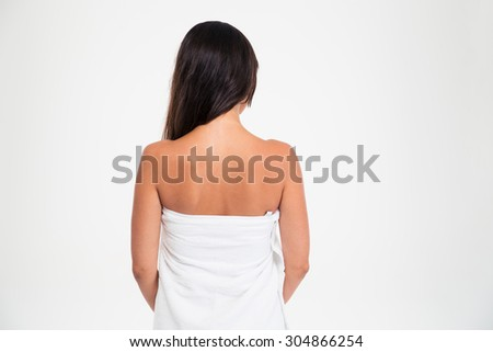 Back view portrait of a woman in towel standing isolated on a white background