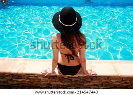 Back view portrait of a young woman sitting on the ledge of the pool - stock photo