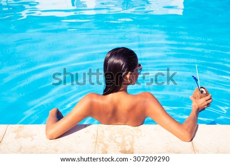 Back view portrait of a young woman standing in swim pool and holding cocktail in coconut outdoors - stock photo