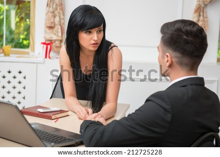 Back view portrait of young business man sitting at the desk and looking at sexy standing colleague, business couple flirting near the table at workplace in office, relationship at work concept - stock photo