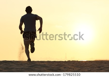 Back view silhouette of a runner man running on the beach at sunset with sun in the background - stock photo
