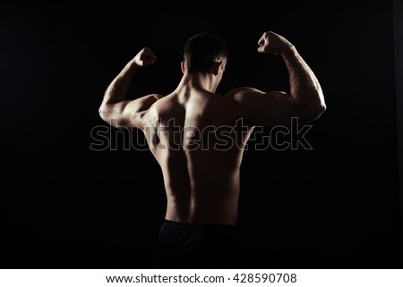 Back view silhouette of hot shirtless athletic guy showing muscles over black background