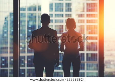 Back view silhouettes of two business partners looking thoughtfully out of a office window in situation of bankruptcy,team of businesspeople in fear or risk watching cityscape from skyscraper interior - stock photo