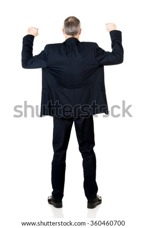 Back view successful businessman with arms up - stock photo