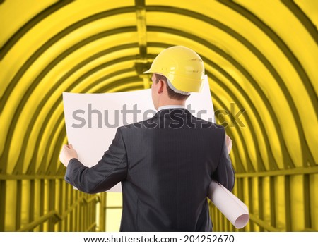 back view torso of architect looking comparing housing blue print paper plant  project  inside on yellow building in perspective background Copy space for inscription - stock photo