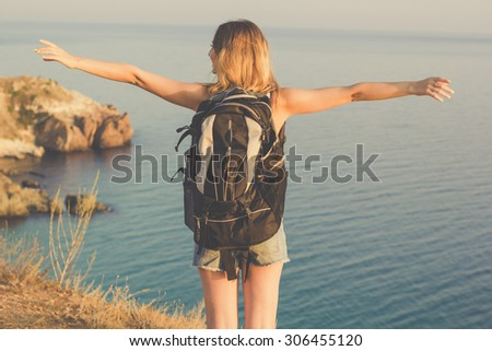 Back view traveler girl is standing on rock edge with backpack over sea view with backpack, summer time - stock photo