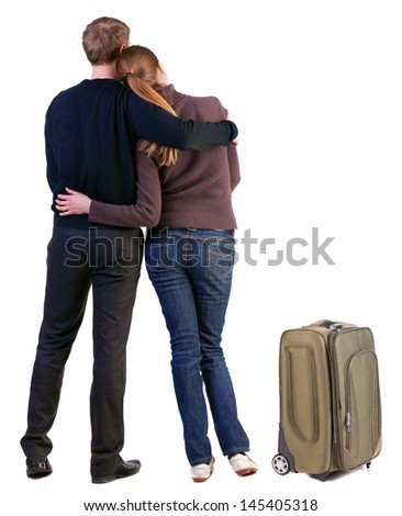 Back view traveling young couple with suitcas look into distance. friendly girl and guy together. Rear view. Isolated over white background. young woman holds the hand of her husband looking away - stock photo