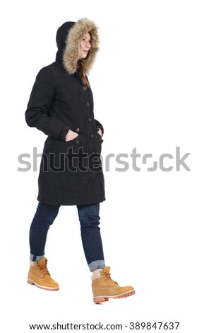 back view walking  woman in winter jacket with hood.  backside view person. Rear view people collection. Isolated over white background. his hands in pockets of girl goes to right