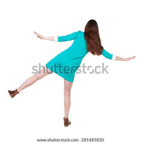 Back view woman Balances waving his arms.    backside view of person.  Isolated over white background. The girl in a blue dress with brown shoes keeps the balance standing on one leg. - stock photo
