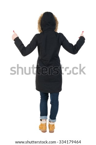 Back view woman  in parka thumbs up. Rear view people collection. backside view of person. Isolated over white background. Girl in a black winter jacket with a hood with two hands showing thumbs up. - stock photo