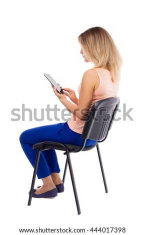 back view woman sitting on chair and looks at the screen of tablet.  Rear view people collection. Blonde in blue pants sitting sideways on office chair and holding horizontally in front of tablet PC - stock photo