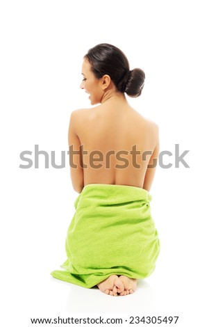 Back view woman sitting wrapped in towel.
