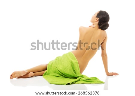 Back view woman sitting wrapped in towel.  - stock photo