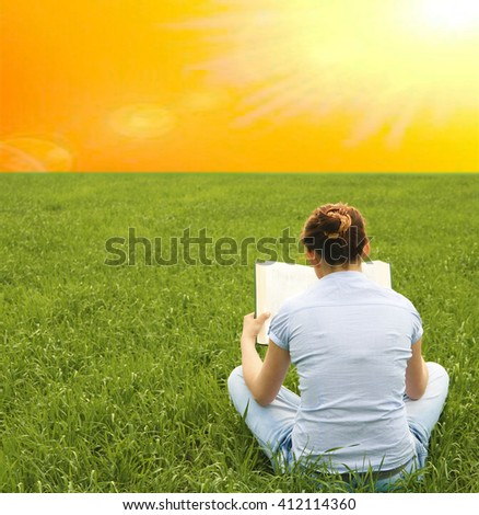 Back view. young adult Girl sitting on fresh green grass background with big book. Woman wearing casual blue dress. Copy space for inscription or other objects. - stock photo