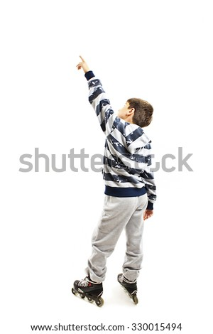 Back view young boy on rollers pointing at wall. Rear view. Isolated on white background  - stock photo
