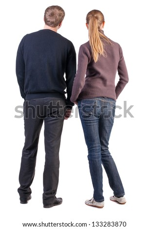 Back view young couple  hug. beautiful friendly girl and guy together. Rear view. Isolated over white. boy and girl  couples face with his hands in his pockets and looking at something interesting - stock photo