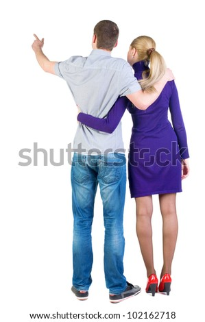 Back view young couple pointing at wall (woman and man). guy in jeans and  girl in blue dress. Rear view people collection.  backside view of person.  Isolated over white background - stock photo
