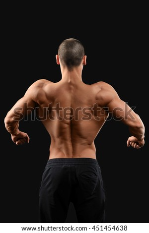 Back work. Male bodybuilder showing off his toned muscular back posing on dark background - stock photo