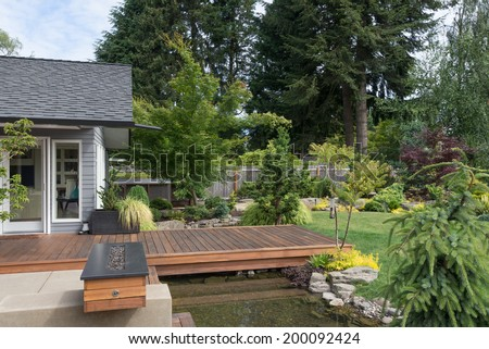 Back yard of a contemporary Pacific Northwest home featuring a deck spanning a creek-like water feature with a landscaped lawn in the background. - stock photo