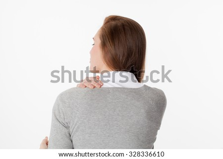backache concept - young woman massaging her shoulder for relief and posture relaxation,back view on white background - stock photo