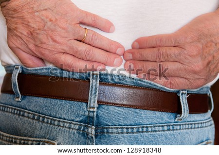 Backache Detail of man in pain with hands on his lower back - stock photo