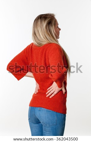 backache, lumbago, scoliosis health problems - young blond woman having a back pain, massaging her lower vertebrae,white background
