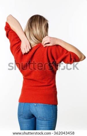 backache, lumbago, scoliosis health problems - young blond woman scratching her back, relaxing her shoulders from back pain,white background - stock photo