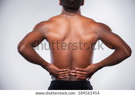 Backache. Rear view of young muscular African man touching his hip while standing against grey background - stock photo