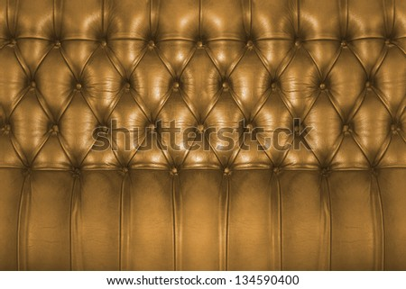 Backboard of a vintage golden brown chesterfield sofa - stock photo