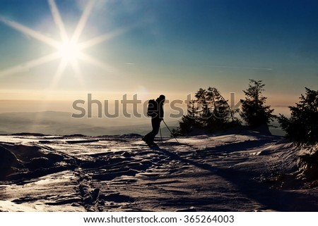 Backcountry skier reaching the summit at sunset