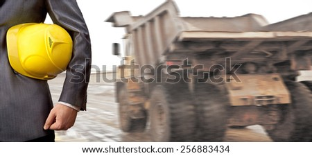 Backdrop of construction worker or torso well dressed engineer hold in hand yellow plastic helmet hardhat on big load transport large empty body truck background Idea logistic concept - stock photo