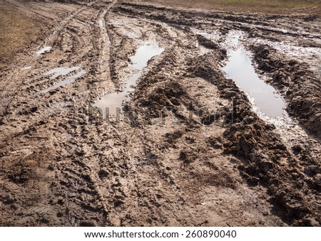 Backdrop of thick viscous slippery tracks from tires on clay off-road in provincial village sunny spring day after rain. - stock photo
