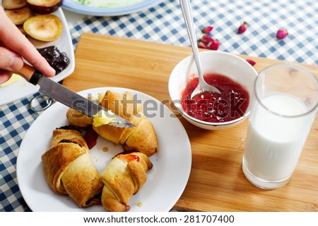 Backed croissants with butter and sweet jam - stock photo