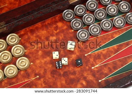 backgammon in the carved box inlaid with skin, counters and bones on a white background - stock photo