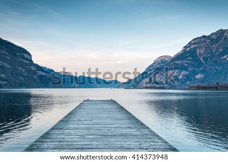 Background as epic mountain landscape.  Lake at sunset  with wooden pier . - stock photo
