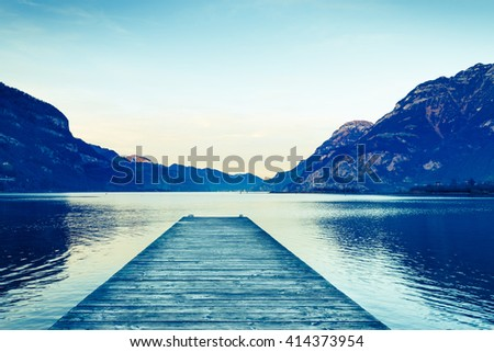 Background as epic mountain landscape.  Lake at sunset  with wooden pier. Bleach bypass effect. - stock photo