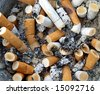 Background Ashtray full of used Cigarette Butts - stock photo