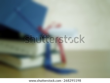 background blur graduation image includes stacked books, blue mortarboard cap with tassel and diploma tied with red ribbon. Not date or year specific, generic application. Horizontal composition - stock photo