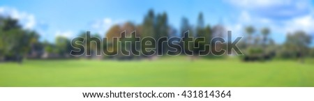 Background blur of summer panorama of expansive green lawn and blue sky dotted with puffy white clouds.  Tall trees including palms, oaks and conifers in the distance.  - stock photo