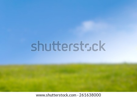 Background blur photograph of grassy hill in Springtime on a bright sunny day with blue sky and fluffy white clouds. - stock photo