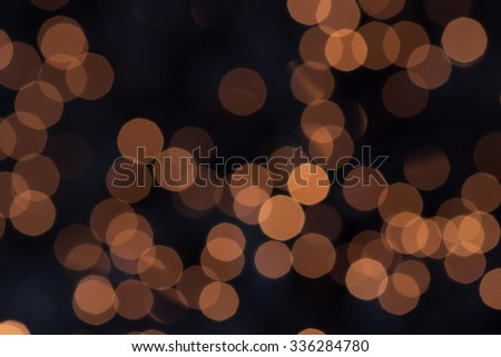 Background bokeh of sparkling defocused party lights twinkling in the darkness conceptual of a celebration, Christmas or New Year - stock photo