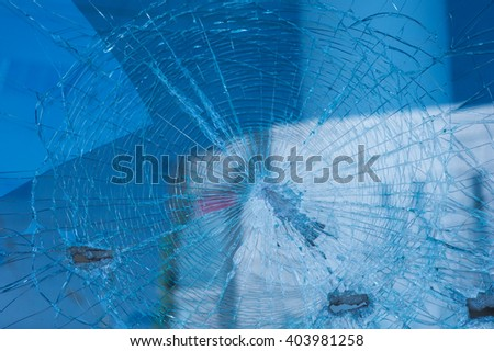 background broken glass from the bullets on facade building - stock photo