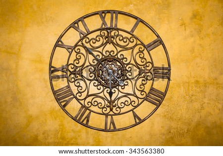 Background brown metal clock on the wall. - stock photo