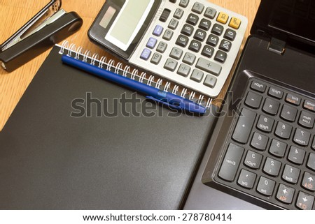 background calculator and notebook on a desk stapler
