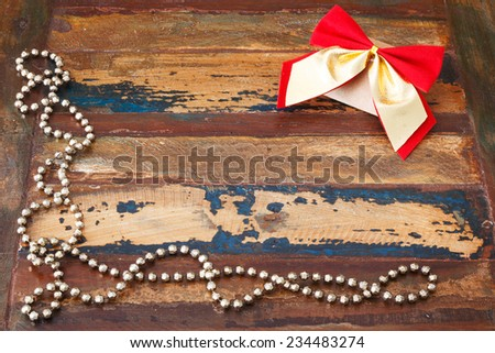 Background: christmas gift package with red golden bow and chaplet. Selective focus on bow. Copy space - stock photo