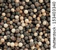 Background close up view of dried whole black and white peppercorns, a pungent aromatic spice and condiment used in cooking - stock photo