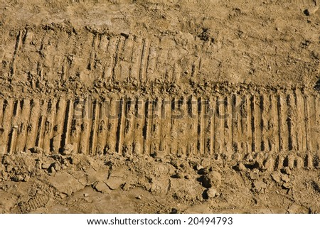 Background closeup of dirt with digger tracks running through it. - stock photo