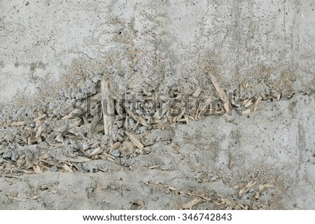 Background concrete wall shows a pattern made from rice straw