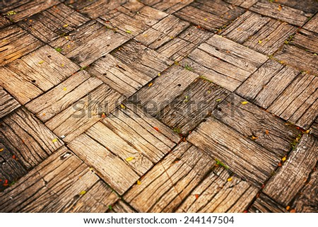 Background, depicting a weathered, parquet style wooden deck with alternating directions of woodgrain. - stock photo