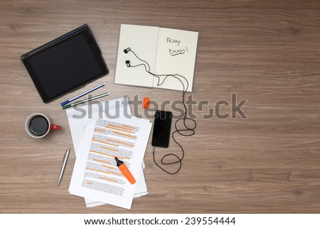 Background, filled with studying materials and copy space on a wooden surface. Items include an electronic tablet,  cup of coffee, pens, markers, a high lighted standard (lorum ipsum) text - stock photo